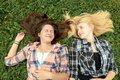 Blonde and brunette friends lying on grass are Stock Photos