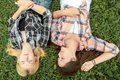 Blonde and brunette friends relaxing on grass are Stock Image