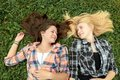 Blonde and brunette friends resting on grass are Stock Photo