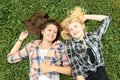 Blonde and brunette girl having break on grass a Royalty Free Stock Photography