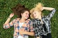 Blonde and brunette girl having rest on grass a Stock Photography