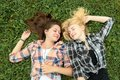 Blonde and brunette girl resting on grass are Royalty Free Stock Image