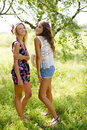 Blonde and brunette smiling girls standing in Royalty Free Stock Photo