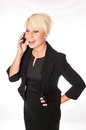 Blonde business woman in a black suit talking on a mobile phone caucasian laughing as she speaks with someone or cell Royalty Free Stock Image
