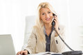Blonde businesswoman phoning in the office a young blond sitting at an desk front of laptop with a smile on her face looking at Stock Photography