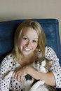 Blonde with cat portrait of a adolescent sitting in blue armchair Stock Photo