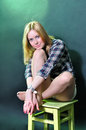 The blonde on a chair smiling beautiful girl sitting and Royalty Free Stock Photography
