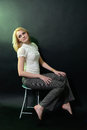 The blonde on a chair smiling beautiful girl sitting Stock Photo
