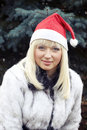 Blonde in Christmas cap and white furcoat Stock Photo