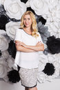 Blonde cute slim fit business woman in grey skirt smiling black and white paper flowers on a background Stock Images