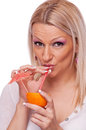 Blonde drinking juice from orange Stock Photo