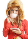 Blonde drinks hot tea girl in fur cap from cup with saucer Stock Image
