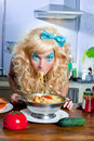 Blonde funny on kitchen eating pasta like crazy Stock Photo