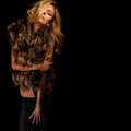 Blonde in fur vest sexy girl on a black isolated background Royalty Free Stock Photos