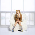 Blonde on furry arm-chair Stock Photography