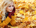 Blonde girl in autumn park with maple leaves fashion beautiful woman leather gloves fall Royalty Free Stock Images