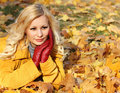 Blonde girl in Autumn Park with Maple leaves. Fashion