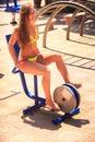 Blonde girl in bikini sits on outdoor bicycle simulator smiles Royalty Free Stock Photo