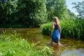 Blonde girl blue mottled dress wade flowing river