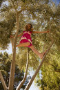 Blonde Girl Climbing High in a Tree Royalty Free Stock Photo