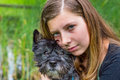 Blonde girl embracing and hugging black dog caucasian teenage in nature with green reed background Royalty Free Stock Images