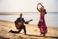 Blonde girl and guitarist on beach at low tide dancing in high heel shoes bearded playing knee Royalty Free Stock Image