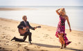 Blonde girl and guitarist on beach at low tide dancing in high heel shoes bearded playing knee Royalty Free Stock Photography