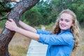 Blonde Girl Holding Tree Trunk...