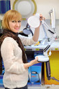 Blonde girl holds white table lamp in shop Stock Photos