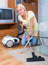 Blonde girl hoovering in living room