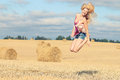 Blonde girl jumps in sloping field Royalty Free Stock Photo