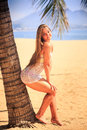 blonde girl in lace leans on palm trunk touches hair on beach Royalty Free Stock Photo