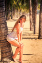 blonde girl in lace leans seat on palm bends body on beach Royalty Free Stock Photo
