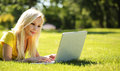 Blonde girl with laptop smiling beautiful woman lying on grass green outdoor Royalty Free Stock Image