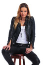 Blonde girl in leather jacket posing in studio background while Royalty Free Stock Photo