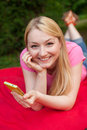 Blonde girl outdoor in the park using her cell phone beautiful Stock Image