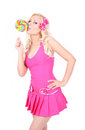 Blonde girl in pink dress licks lollipop Royalty Free Stock Photo
