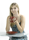 Blonde girl drinking coffee out of a red mug against a white background while sitting at a modern glass desk Royalty Free Stock Photo