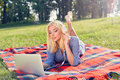 Blonde girl is relaxing in a park and using laptop Royalty Free Stock Photo