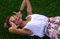 Blonde girl in round glasses on the grass lays Royalty Free Stock Image