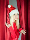 Blonde girl Santa Claus opens curtain Royalty Free Stock Image