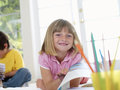 Blonde girl sitting on floor at home near brother holding drawing smiling portrait Royalty Free Stock Photos