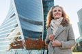 Blonde girl smiling and looking at sky in business district Royalty Free Stock Photo