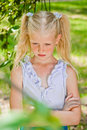 Blonde girl standing in a garden with hands clasped looking at green the floor and takes offense Royalty Free Stock Photos