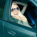 Blonde girl with sunglasses sitting in the car eyewear concept magnificent blue colored outdoor shot Stock Images