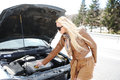 Blonde girl trying to fix broken car Royalty Free Stock Photography