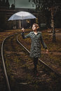 Blonde girl with umbrella balancing on rail retro style Royalty Free Stock Images