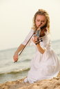 The blonde girl with a violin outdoor music lover on beach playing love of music concept Stock Photography
