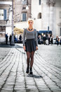 Blonde girl walking on the street in the city wearing a skirt. Royalty Free Stock Photo