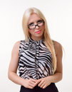 Blonde girl wearing glasses the cute young woman is looking over the top of her at the camera Royalty Free Stock Image